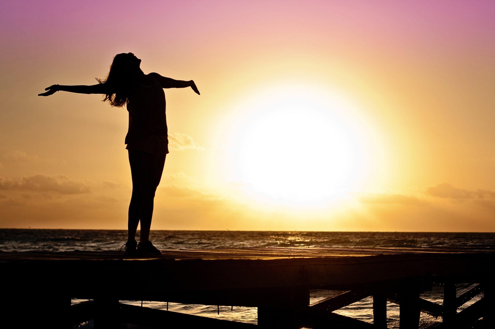 happy woman breathing in sunset glow